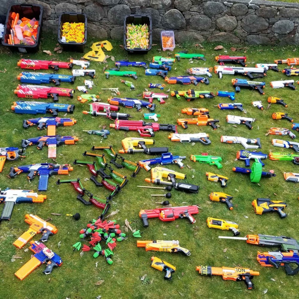 Lots of nerf blasters nerf guns, nerf darts laid out on the grass